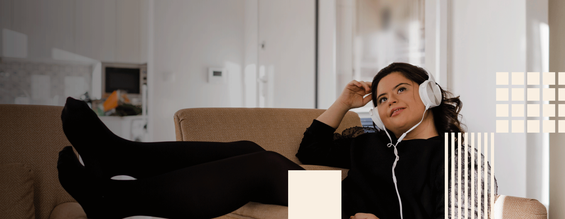 lifestyle image of a woman laying on a couch and listening to music through in-ear headphones